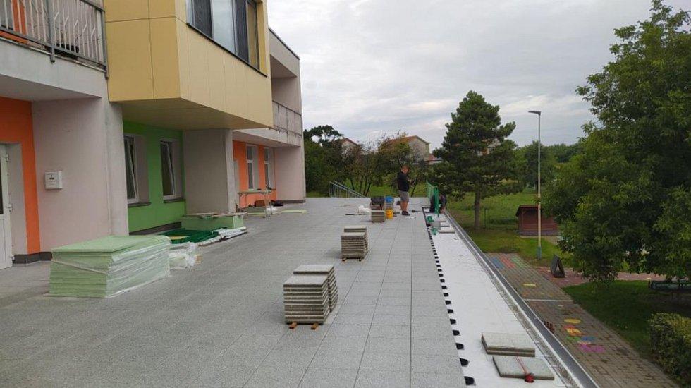 Řemeslníci opravují terasu nad kuchyní a technickými místnostmi v mateřské škole ve Velkých Pavlovicích.