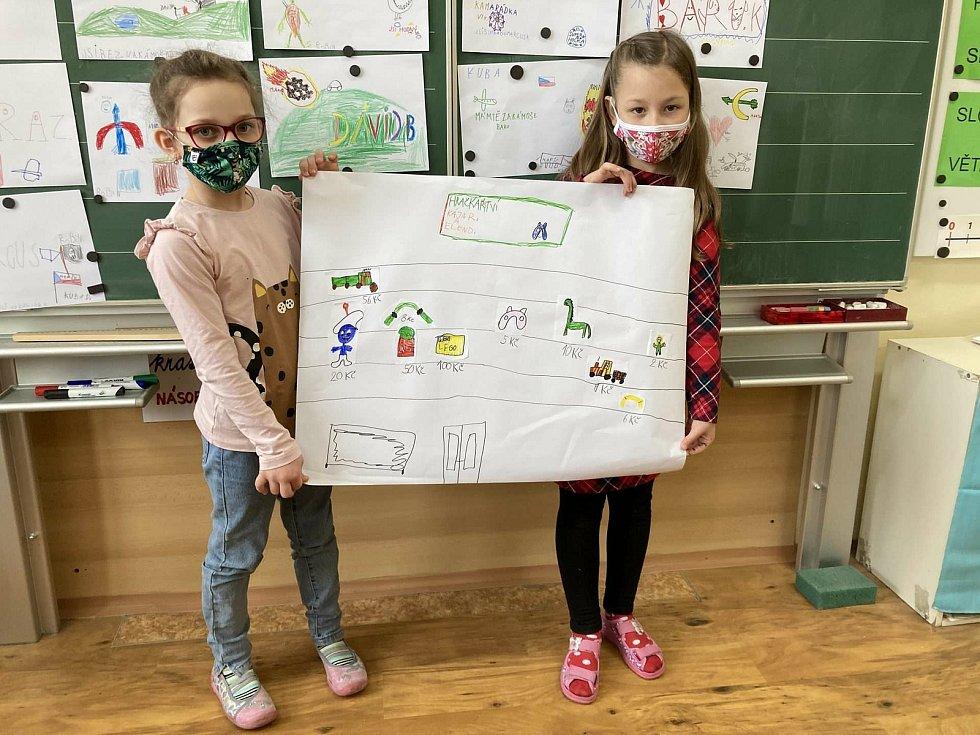 Malí školáci ukazují své práce.