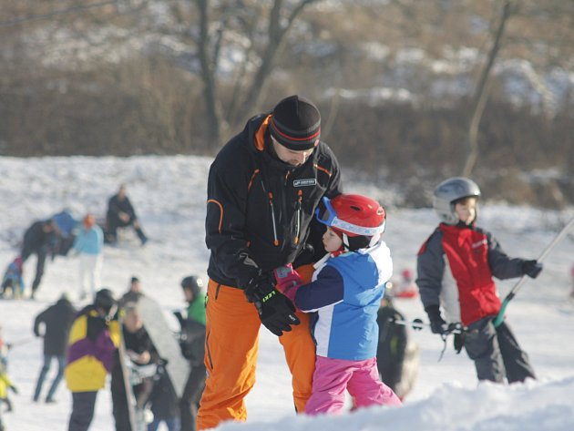 Na pomu, která vyváží malé i velké lyžaře nad kopec, stojí v pátek dopoledne fronty. Instruktoři i rodiče se zejména věnují dětem od tří let nahoru. Rozběhla se i školička pro děti, které se nedostaly do dlouhodobého kurzu.