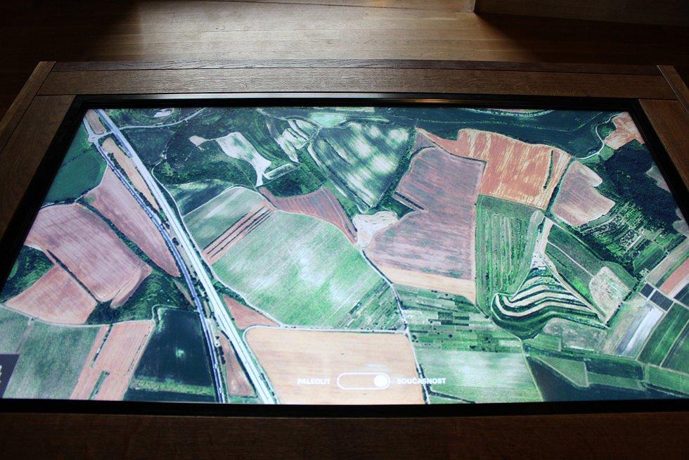 Součástí expozice je i dotyková tabule, na které si mohou návštěvníci prohlédnout okolí archeoparku v paleolitu.