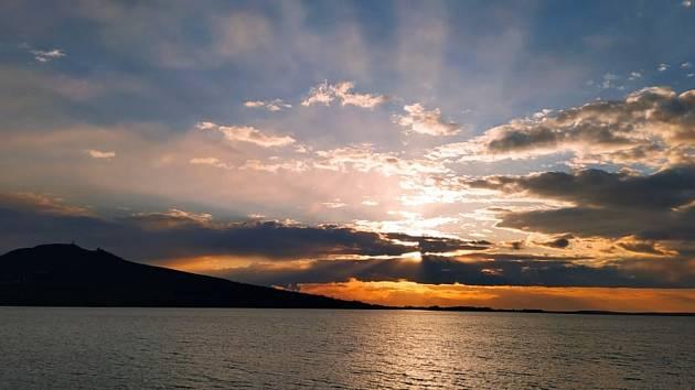 Na vodní hladinu dopadají poslední paprsky zapadajícího slunce.