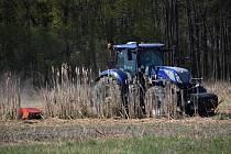 Traktor zemědělského družstva Zemos z Velkých Němčic kosí rákos v místech mokřadu u Uherčic.