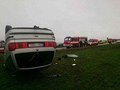 Vůz skončil po nehodě převrácený v poli.