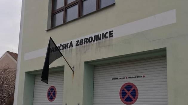 Černý prapor u budovy dobrovolných hasičů v Rakvicích.