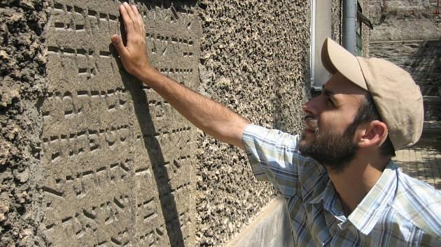Daniel Polakovič před jedním z nahrobků zazděným do fasády domu