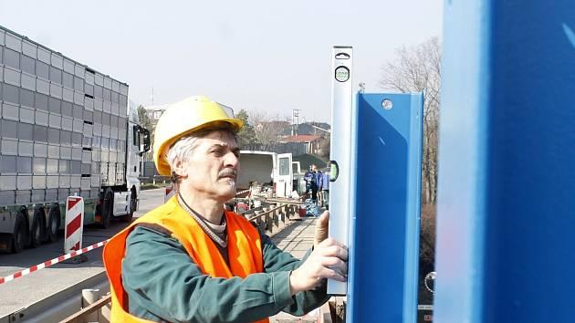 Pracovníci specializované firmy vyěmňují nevyhovující protuihlukovou bariéru na mostě u Dobšic za novou.