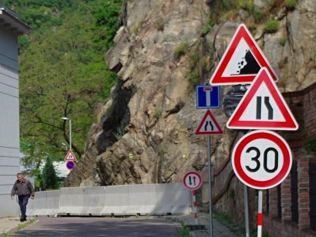 Na padajcí kameny ze skály v ulici U Obří hlavy upozorňují nyní značky a bariéry.