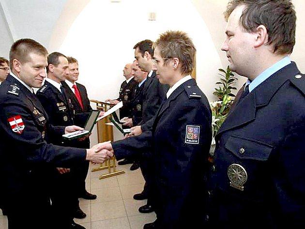 Plukovník Mojmír Pavelka (vlevo) předává ocěnění svým podřízeným.