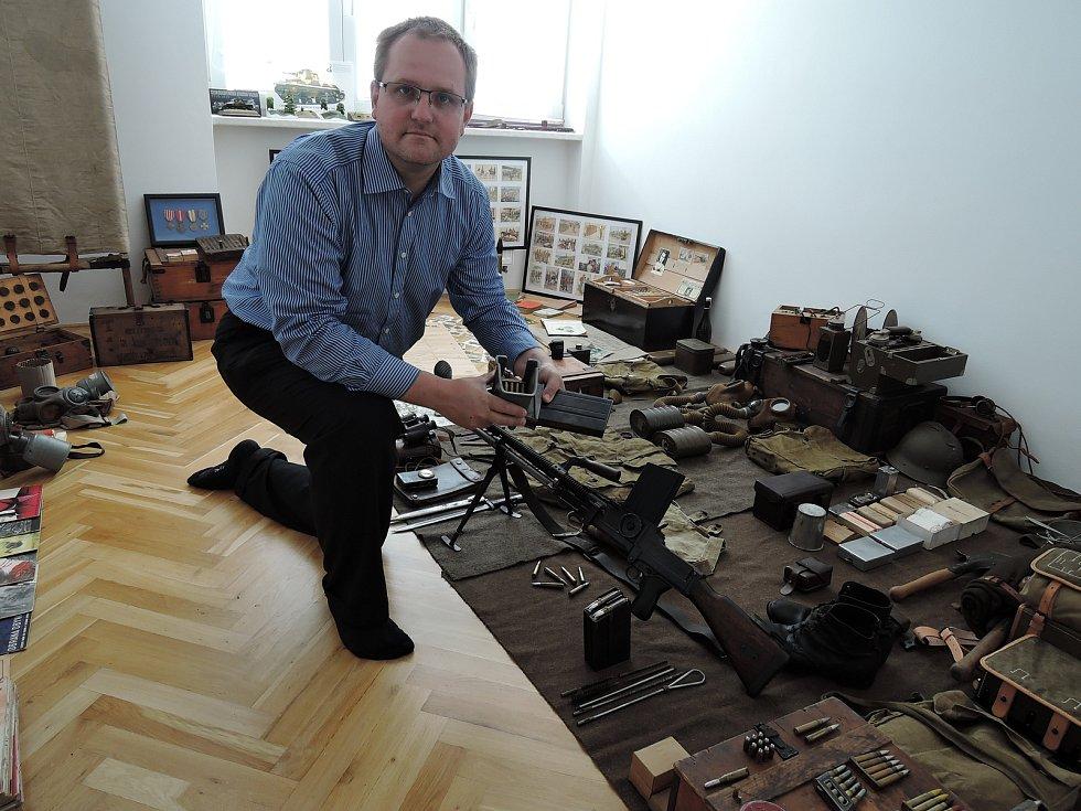 Martin Černý v depozitu, kde se ukrývají věci, pro které v současné době není místo na vystavení. V ruce má sběratel plničku zásobníku pro lehký kulomet vz. 26.