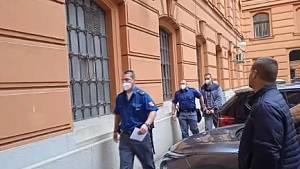 Policejní eskorta vede Tomáše Valihracha k soudu.