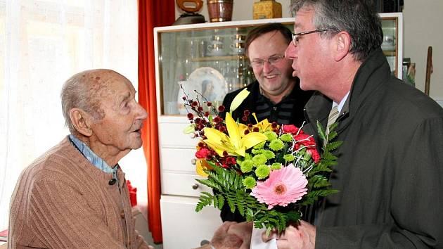Pan Viktor Kohout oslavil 17.12. sté narozeniny. Blahopřeje Ladislav Koukal ze správy sociálního zabezpečení, vpozadí starosta Tavíkovic Libor Kosour.