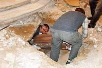 Archeologové vyzdvihují z krypty dětskou rakev.