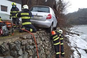 Muž, který zůstal viset v autě nad vodou, v nemocnici zemřel.