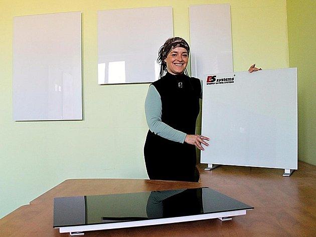 Tepelné panely vyrábí firma ES Systems ze čtyřmilimetrového kaleného skla v bílém a černém provedení a samozřejmě v různých velikostech podle jejich výkonu. Na snímku je představuje Hana Čertková, která má na starosti jejich prodej.