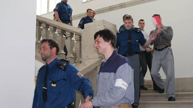 Čtveřici obviněných v poutech přivedla včera ke znojemskému soudu vězeňská eskorta přímo z výkonu trestu, dva další seděli už v soudní síni, posledního obviněného soudili v nepřítomnosti.