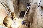 Arechologové při čištění zdí vlčí jámy.