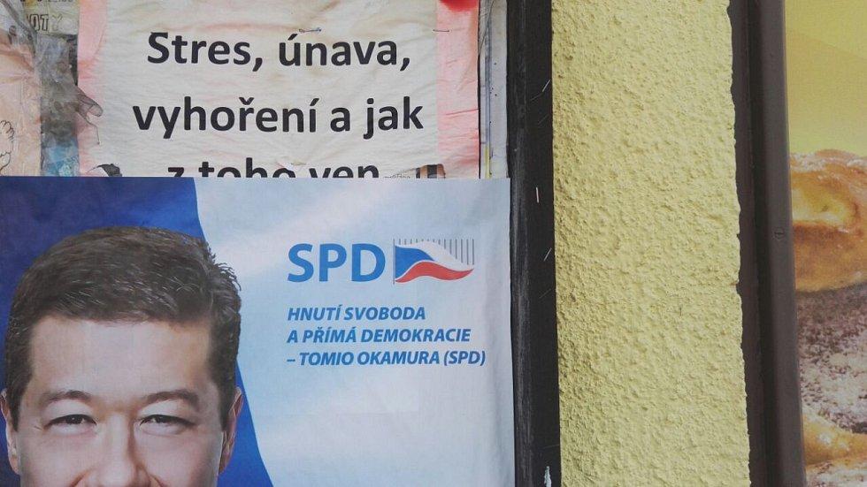 Kouzlo nechtěného - na plakátovací ploše u obchodu v Dobšicích na Znojemsku se překrývá plakát Tomia Okamury se starší inzercí.