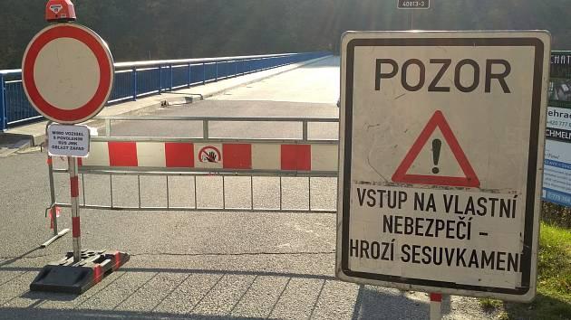 Zákaz pro řidiče, vstup na vlastní nebezpečí pro chodce. Na silnici padá kamení