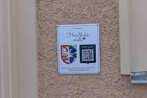 Cedule se znakem města a QR kódem u vchodu do miroslavské radnice.