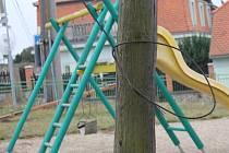 Dětské hřiště na znojemském Hradišti: z plotu kouká nebezpečný hrot, přímo na hřišti visí i rezavý drát ze sloupu.