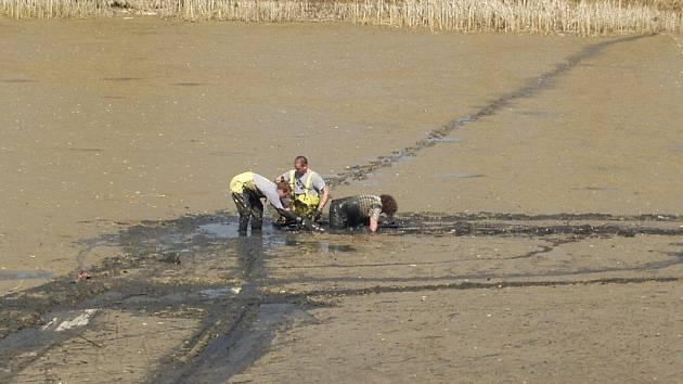 Hasiči vytahují studenta z bahna.