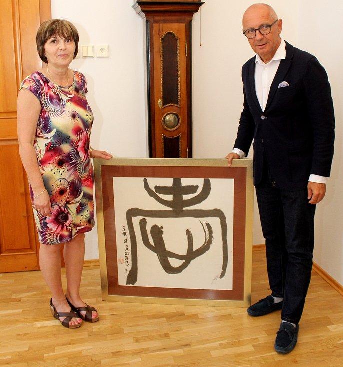 Velvyslanec Libor Sečka předává ředitelce Vladimíře Durajkové kaligfarii, jeden ze sto šesti darovaných předmětů ze svých pracovních cest po světě.