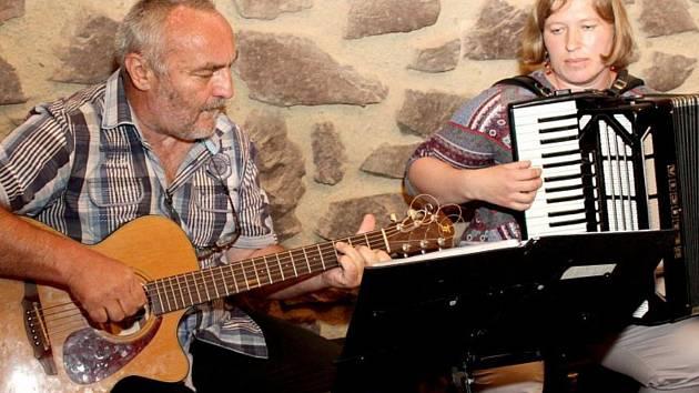 Duo Tana při vystoupení. Martin Škorpík hraje na kytaru a zpívá, Zuzana Křížová hraje na akordeon.