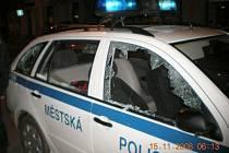 Rozbité okno na policejním autě.