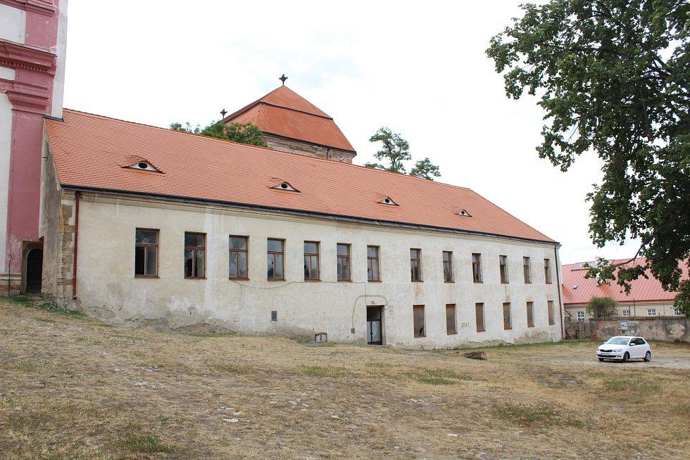 Šedá budova staré školy v areálu Louckého kláštera ve Znojmě má nyní rozbitá okna a městu dělá spíš ostudu.