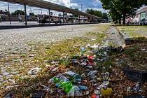 Cestující a kolemjdoucí si všímají nepořádku panujícího v blízkosti starého autobusového nádraží ve Znojmě. Po zemi se válí plastové lahve, kelímky od kávy a další odpadky.