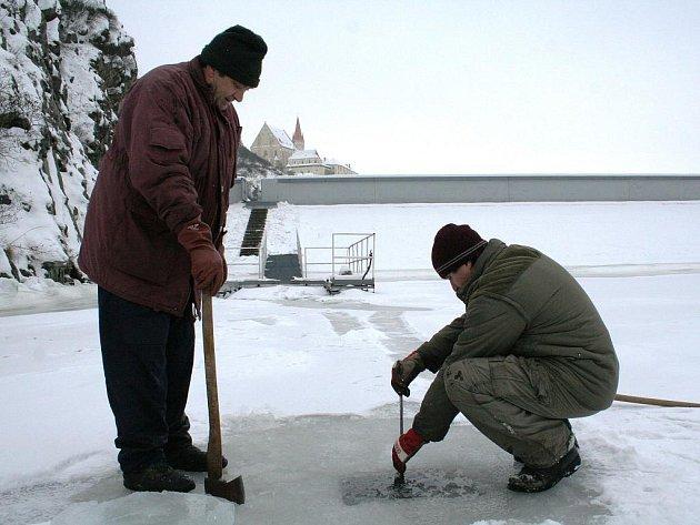 Hrázní měří tloušťku ledu na znojemské přehradě.