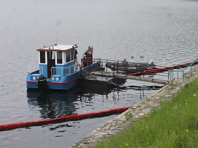 Policejní potápěči zjišťují původce ropné skvrny na přehradě.