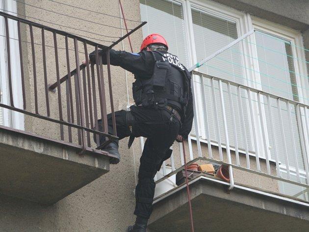 Městská policie slaňuje do zavřeného bytu.