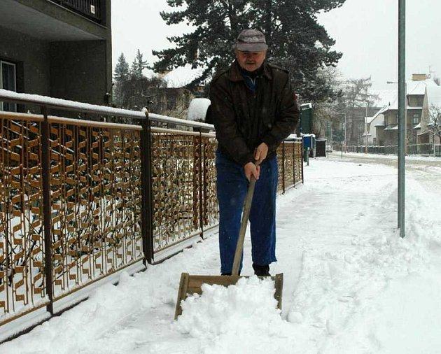 Úklid sněhu na chodníku před domem