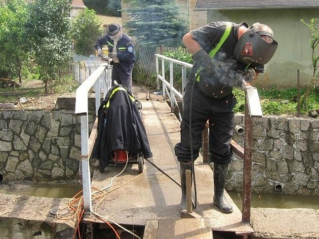 Dobrovolní hasiči z Jezvé neváhali pomoci s opravou mostků poničených bleskovou povodní v Dolních Habarticích na Děčínsku.