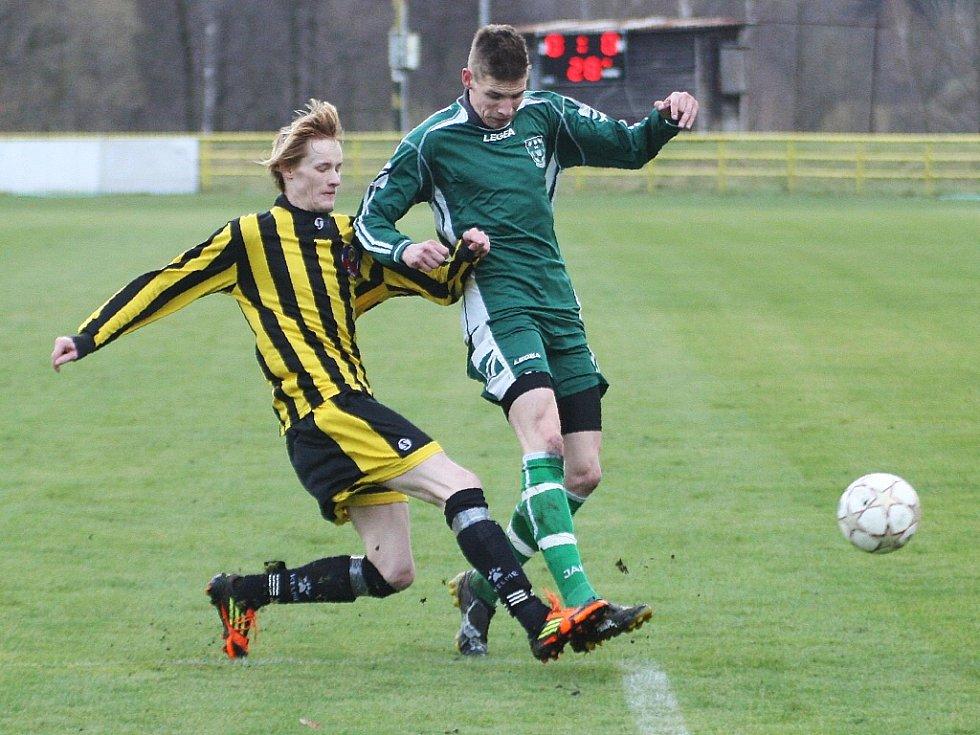 Stále první v tabulce krajského přeboru jsou fotbalisté Nového Boru. Studnička odvrací míč před Demkem do bezpečí.