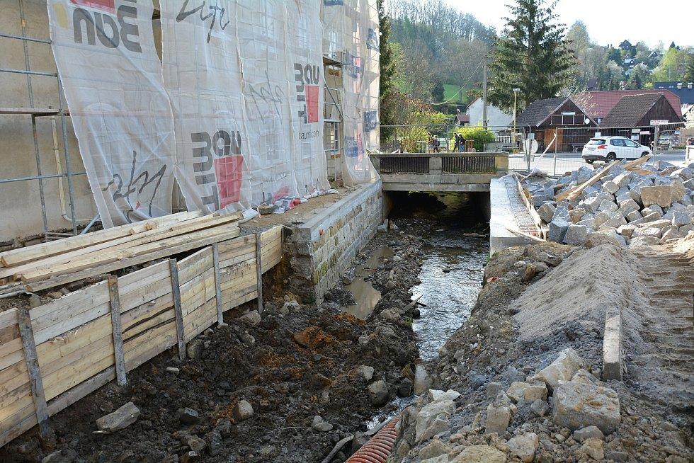 Stavbaři se potýkají s potokem u nároží hostince U Slunce.