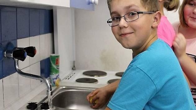 Žák kravařské školy myje nádobí.