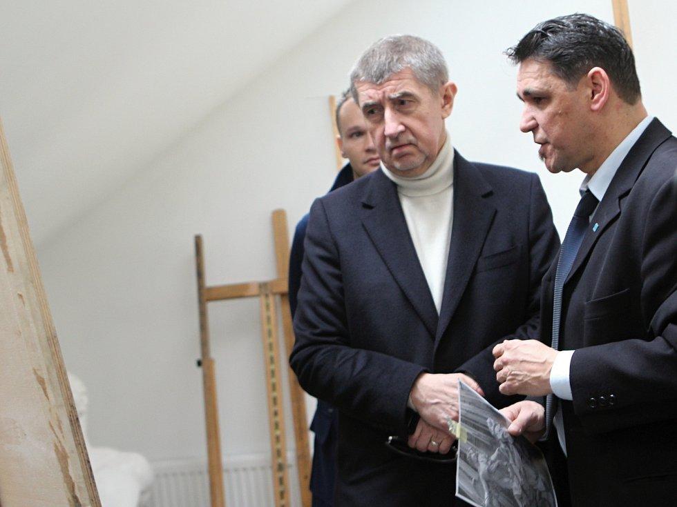 Andrej Babiš s ředitelem SUPŠS v Kamenickém Šenově Pavlem Kopřivou obdivují výtvarné práce studentů školy. Jedna ze studentek se na návštěvu vládních činitelů dobře připravila.