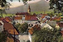 Stráž pod Ralskem je na obrázku zachycená tak, jak vypadala v roce 1910. V pozadí je vidět Ralsko.