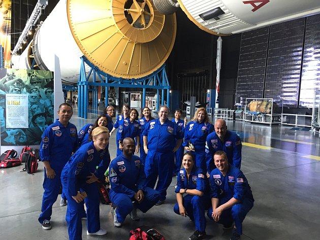 Učitel Jan Kacafírek (vpravo dole) se svou skupinou pod raketou Saturn V.