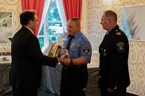 Starosta Jaromír Dvořák předává dárkový balíček Josefovi Pavlasovi, který je společně s velitelem Jiřím Zemancem nejdéle sloužícím strážníkem u novoborské městské policie.