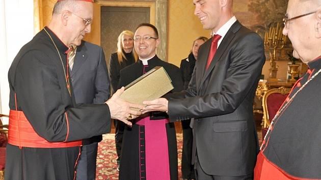 Kardinál Tarcisio Bertone přebírá křišťálový pohár pro papeže z rukou Jan Šolta, manažera značky Pilsner Urquell.