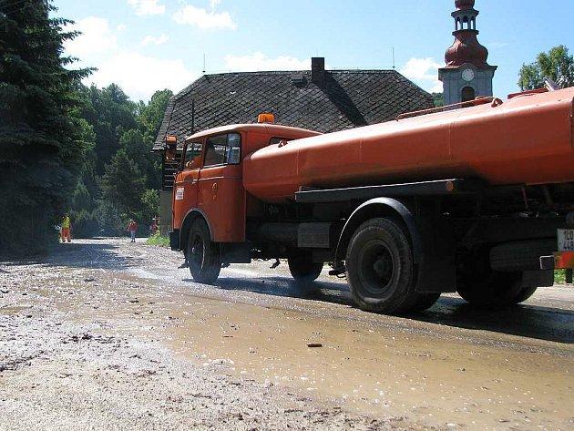 Během noční bouřky voda zaplavila náves ve Velenicích. Ráno zbyly po deštích nánosy bahna, které odklízeli pracovníci krajské správy silnic a dobrovolní hasiči ze Zákup.