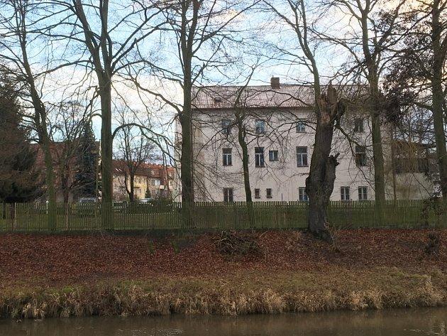 Zadní pohled na komplex budov Farní charity v Dubické ulici od břehu Ploučnice.