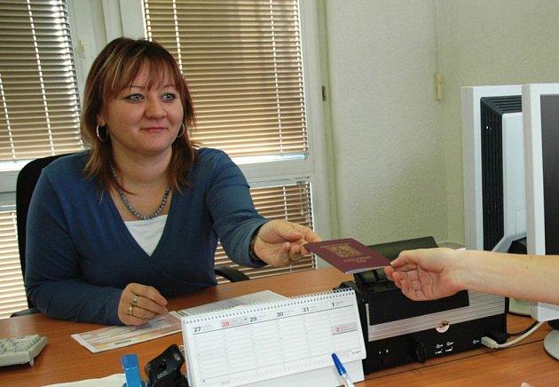 Úřednice správního odboru novoborského městského úřadu Romana Slánská vrací žadatelce pas se zapsaným dítětem.