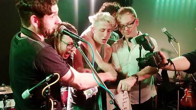 Členové kapely polévají desku sektem.