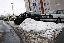 Parkoviště, které je i v létě přecpané, má nyní menší kapacitu kvůli kupám odhrnutého sněhu.