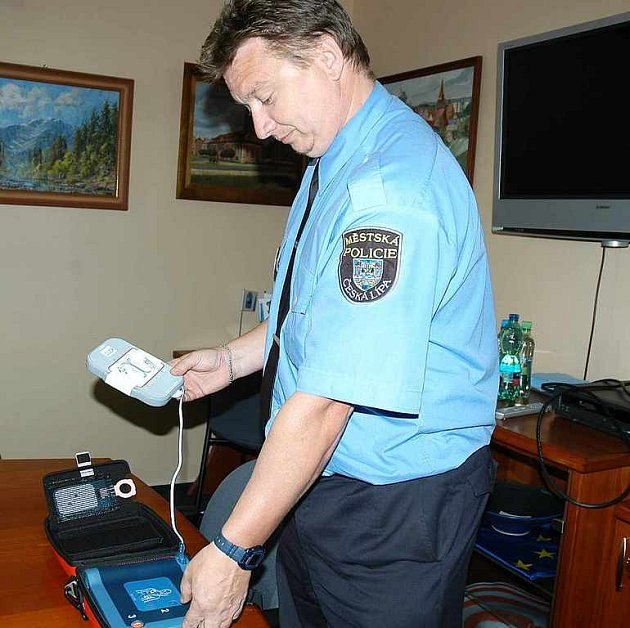 Vedoucí hlídkové služby městské policie Václav Bína předvádí nový defibrilátor, který má MP ve svém vybavení.