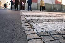 Asfalt a dlažba. Tyto dva povrchy si spolu zvlášť v historických centrech měst příliš nerozumějí.